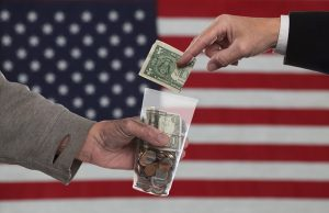 American Gothic Series/suited man's hand placing dollar bill into money-filled plastic cup held by dirty man's hand against soft-focus US flag background